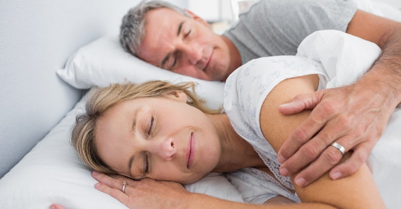 couple-sleeping-and-spooning-in-bed-in-bedroom-at-home