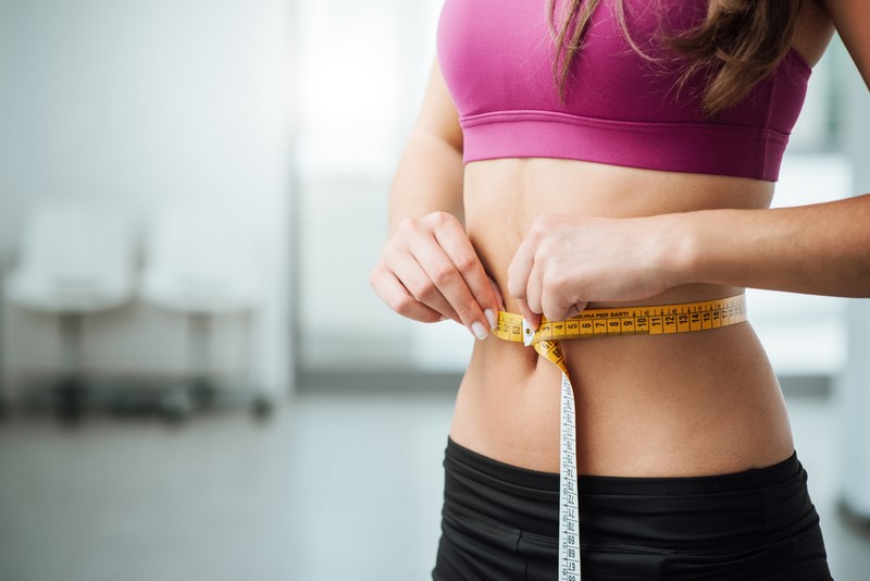 slim-young-woman-measuring-her-thin-waist-with-a-tape-measure-close-up