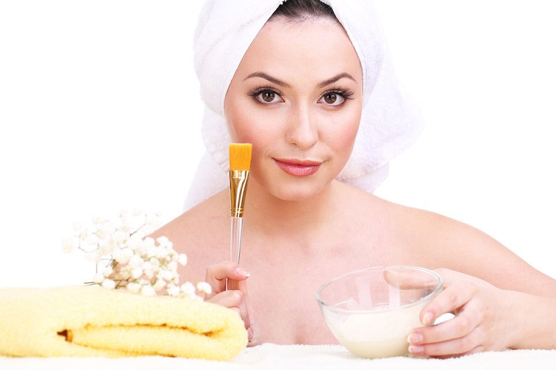 beautiful-young-woman-with-cream-for-face-mask-and-towel-on-her-head-isolated-on-white
