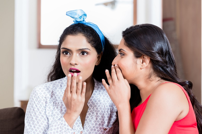 young-woman-whispering-to-her-best-friend-gossips