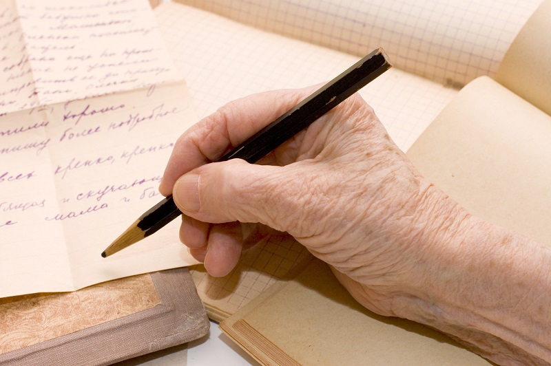the-old-hand-writes-the-letter-a-pencil