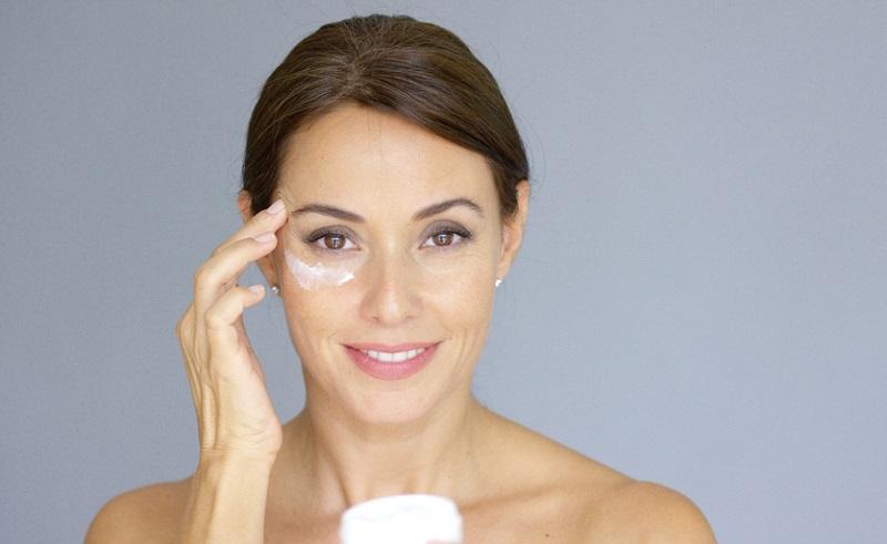 beautiful-young-woman-applying-face-cream