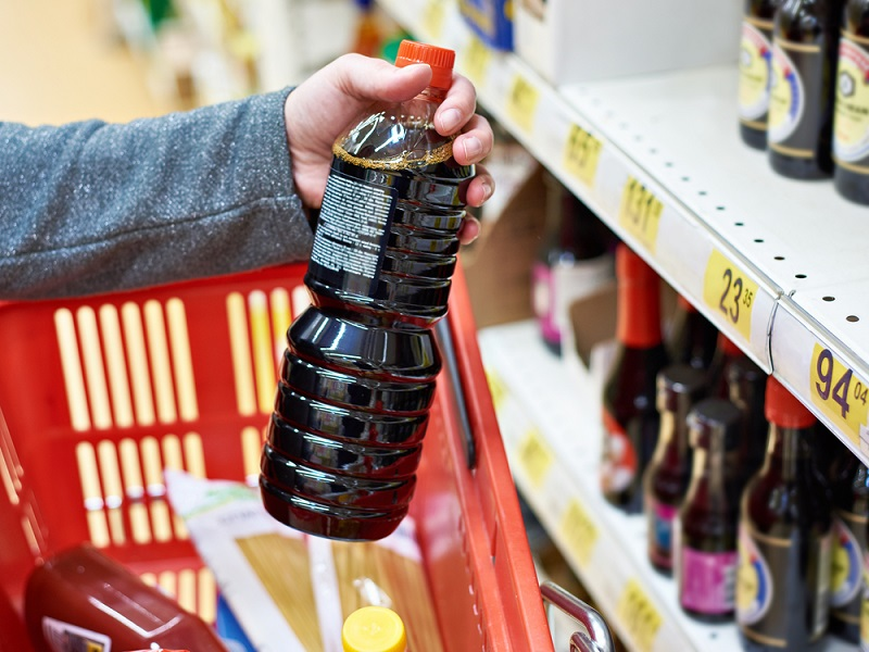 soy-sauce-bottle-in-hand-buyer-at-grocery-store