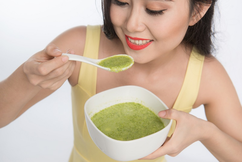 portrait-of-asian-woman-eating-holding-a-plate-of-green-vegetabl